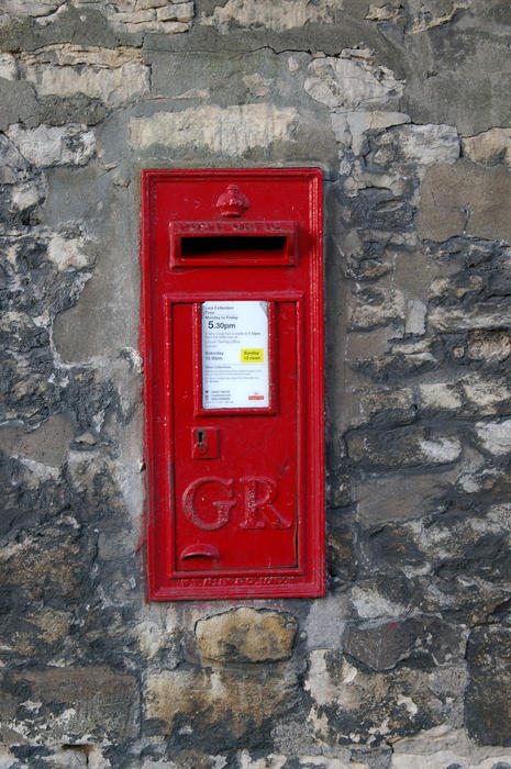 a red uk posting box mounted in a stone wall
