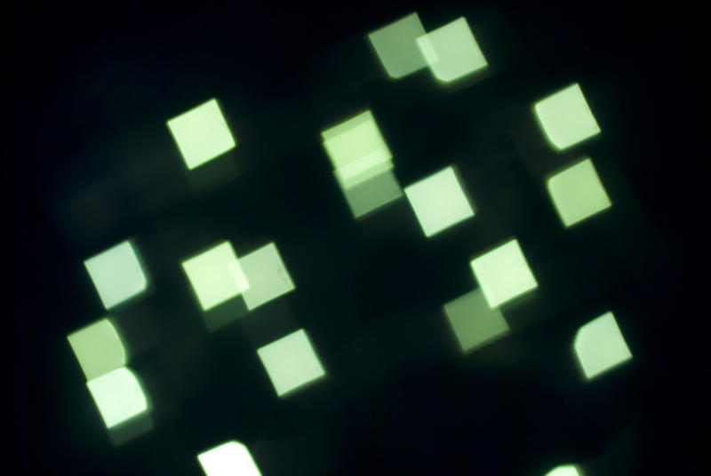 defocused camera effect, green lights create square bokeh