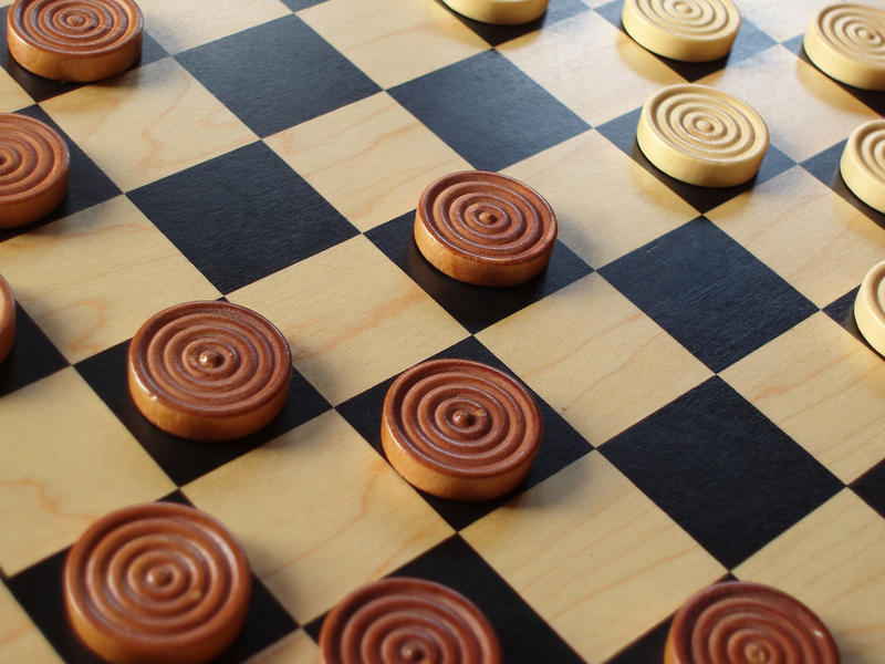 a wooden draughts or checkers with wooden counters