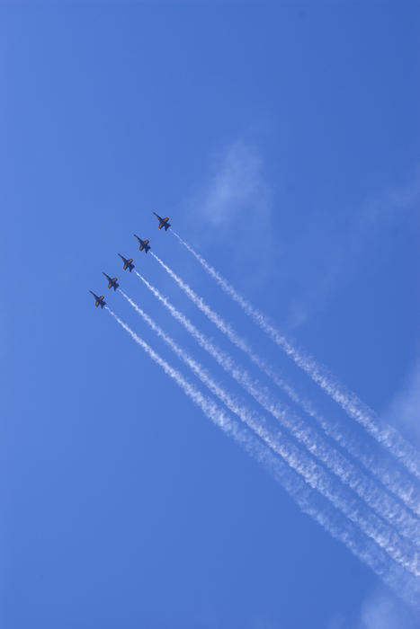 5 blue angels flying high in the sky with smoke trails