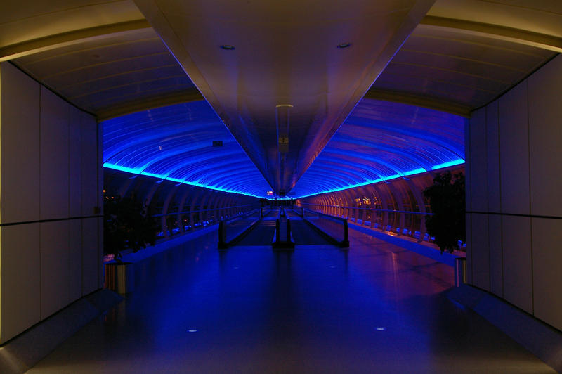 a blue lit walkway between terminals at manchester airport, uk