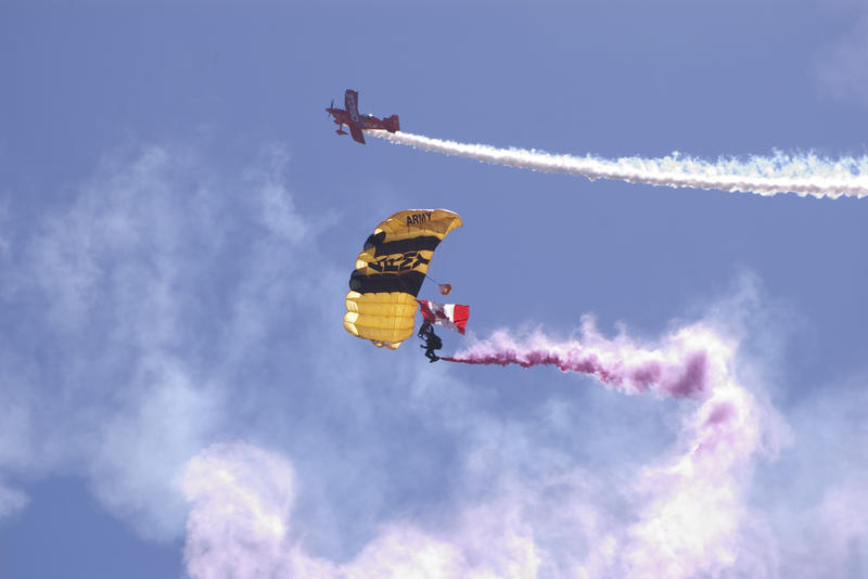 a plain and parachutist at an air show