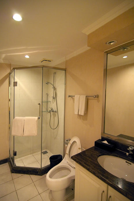 a clean modern bathroom with shower, toilet and wash basin