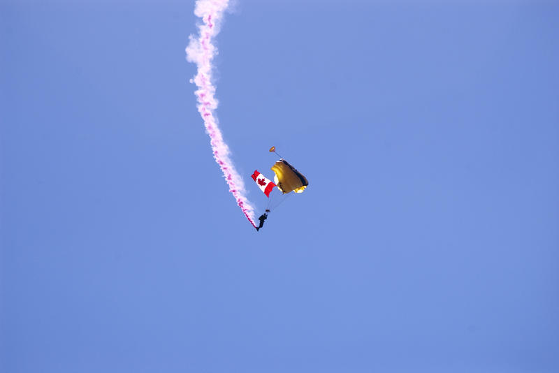 a paratrooper with a canadian flag at an air show