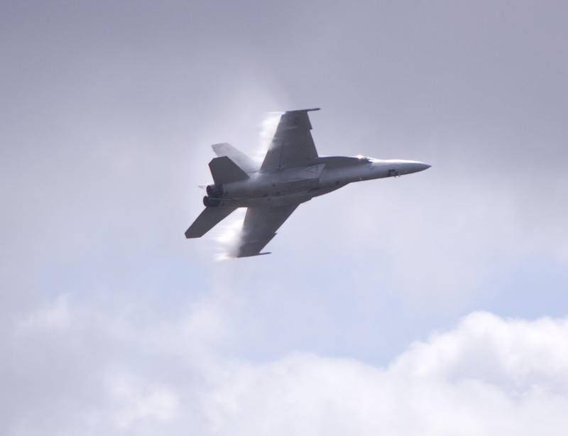 Boeing FA-18 Super Hornet multirole fighter aircraft with lines of vapour formed at the trailing edge of the wings