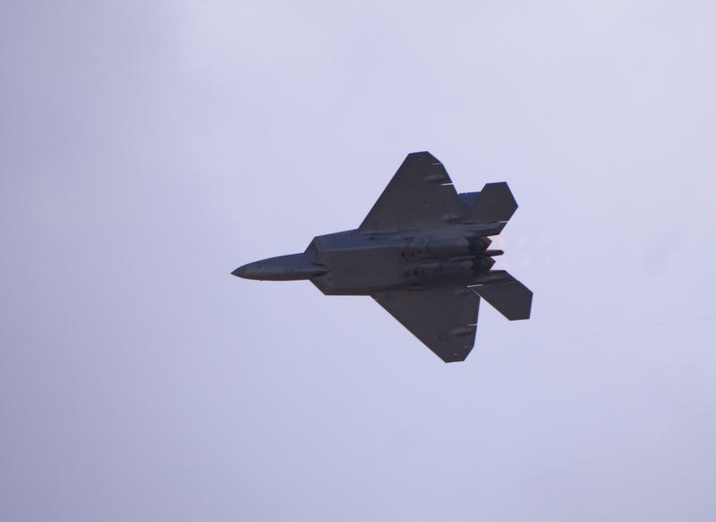 A bottom view of a F-22 Raptor as it flys overhead