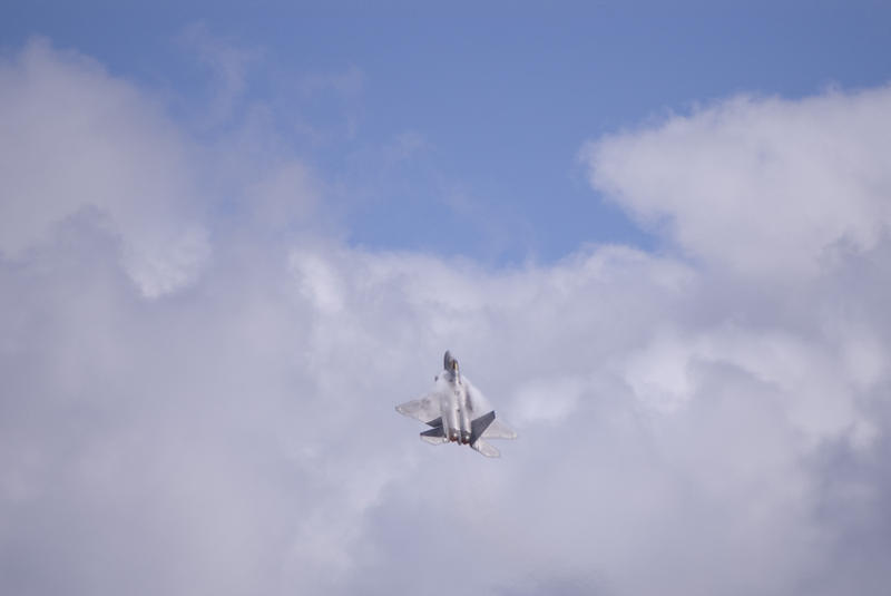 Lockheed Martin F-22 Raptor Aircraft performing a steep climb and creating vapour trails from the leading edges of its wings