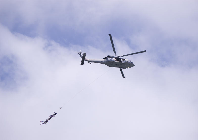 A helicopter with three divers 'flying' at the end of a line