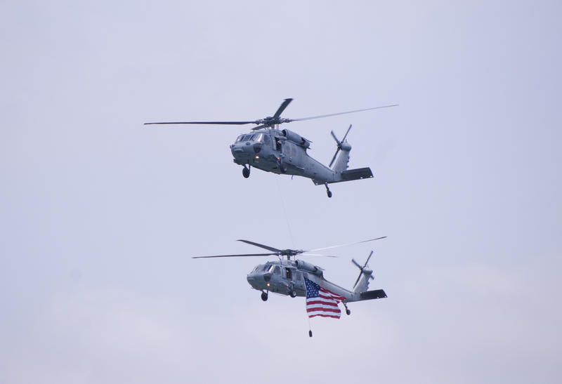 a couple of helicopters flying the strs and stripes at an air show