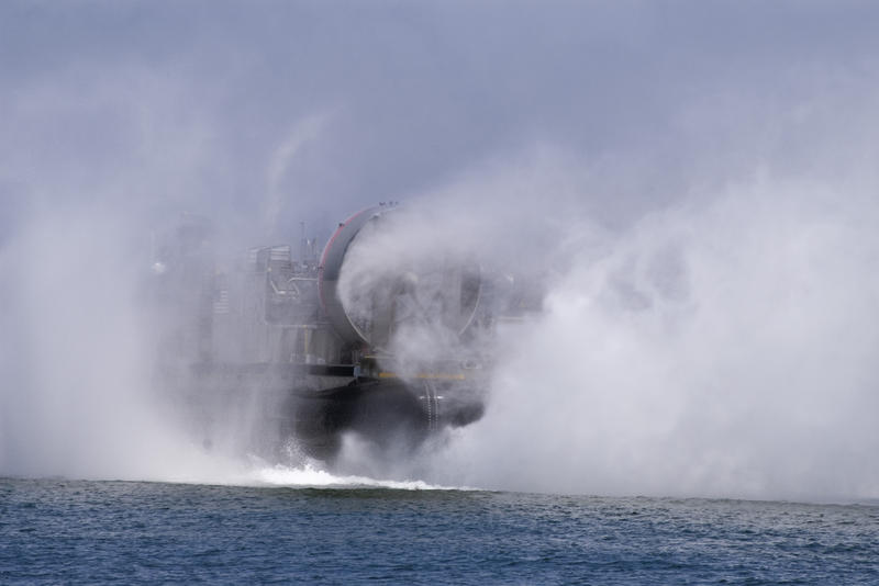 large fans propelling a navy hovercraft