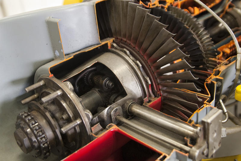 a jet engine with cut away sections to see the turbine blades inside