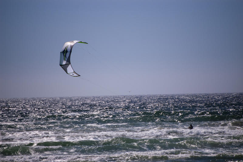 a kitesurfer skirting along the water