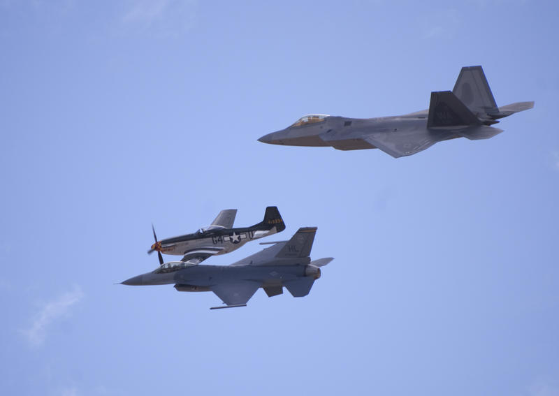 three planes in flight, an on P-51 mustang with propeller, and modern FA18 hornet and F22 raptor jet aircraft