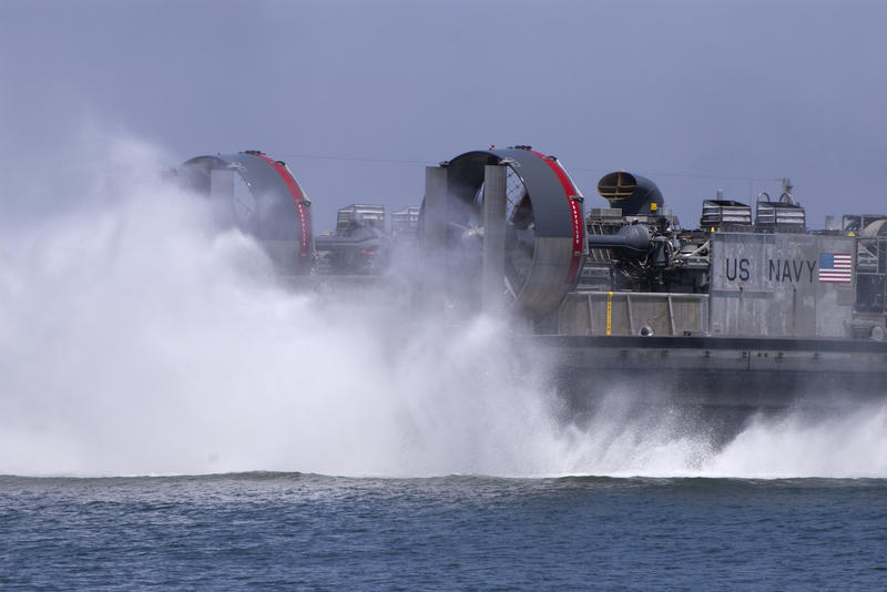 water kicked up from the fans at the back of a navy hovercraft
