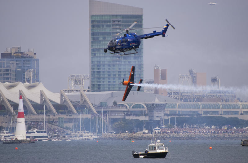 editorial use only : red bull air race san diego, a plane makes a sharp turn filmed by a camera helicopter
