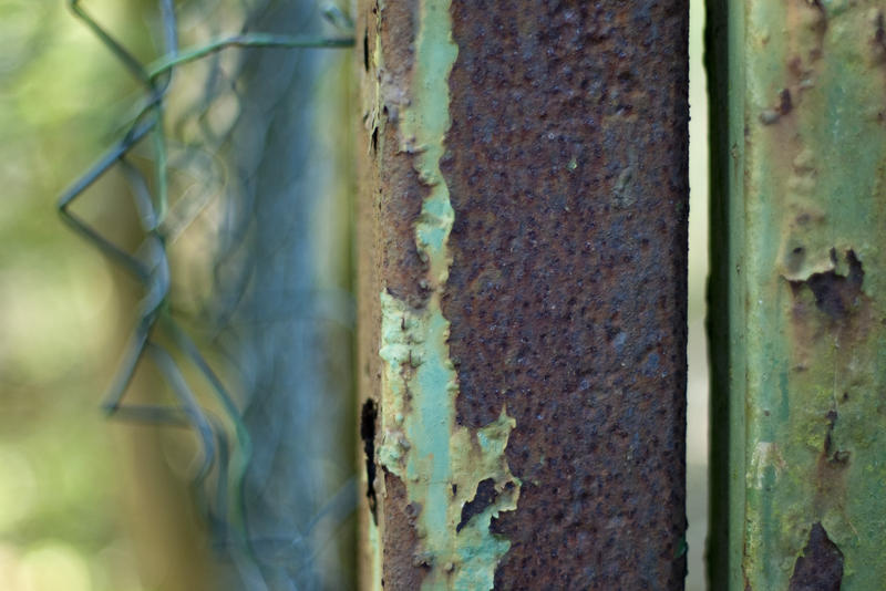 close up on a rusted metal gate and damaged chain link wire fence