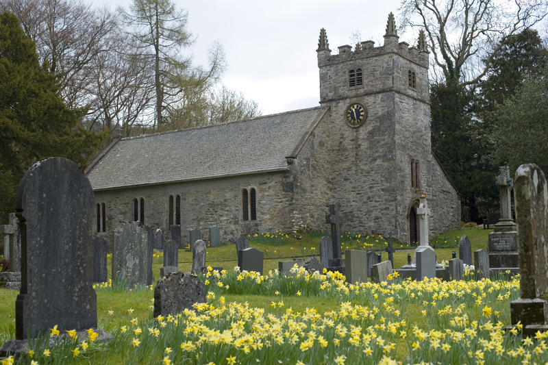 the outside of a small village church with springtime daffodils in the churchyard