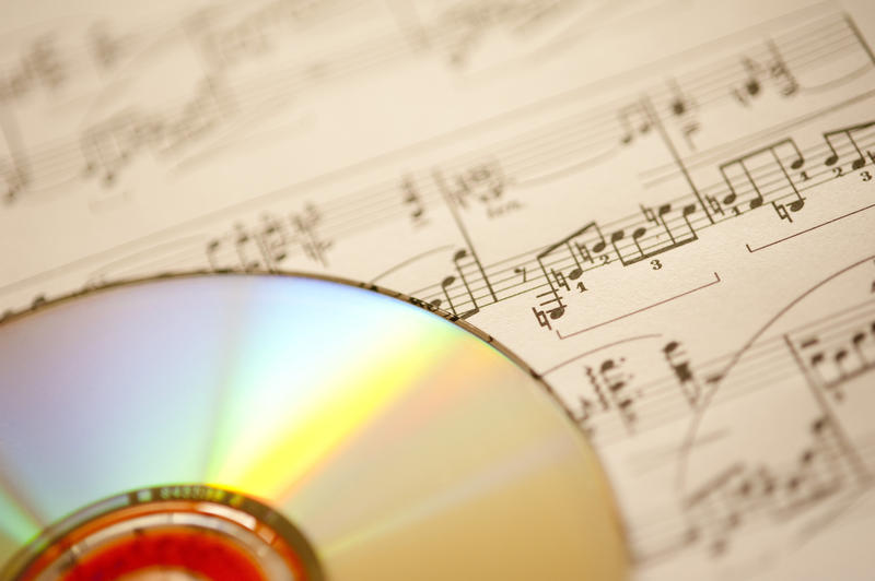 a background image of a piece of sheet music an a CD pictured with a narrow depth of field