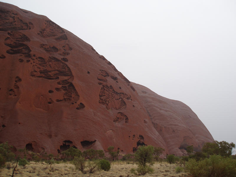 the side of uluru (ayres rock) on a rainy day