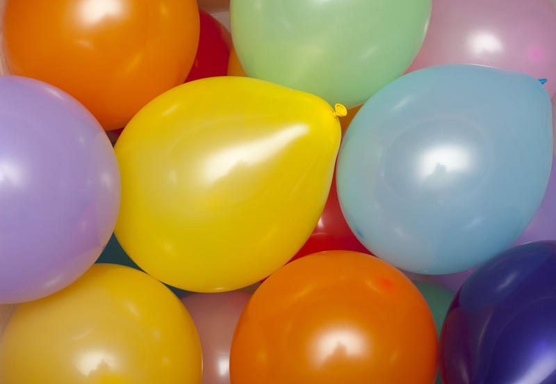 a background of various colored party baloons