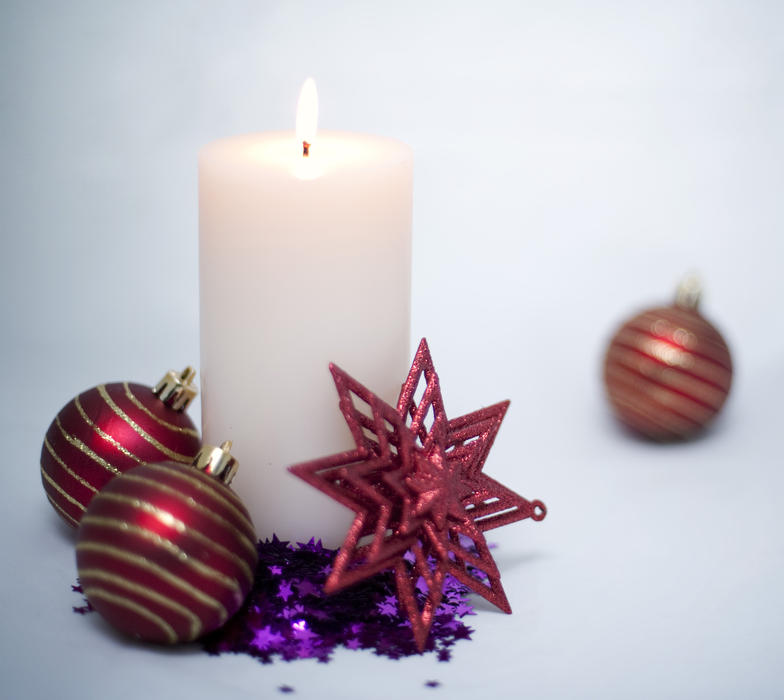 a still life of a lit christmas candle and decorations on a bright light background