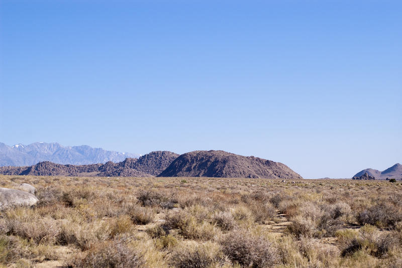 a flat desert landscape with distant hills and mountain ranges