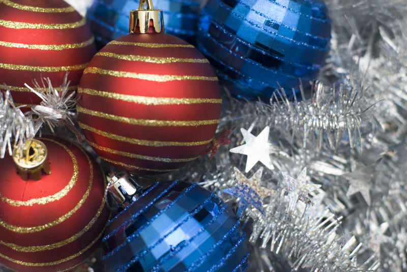 an assortment of reflective christmas baubles on a background of silver tinsel