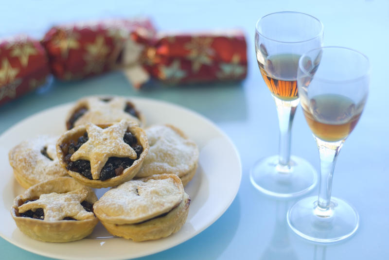 a plate of christmas mince pies, sherry glasses and a pulled cracker