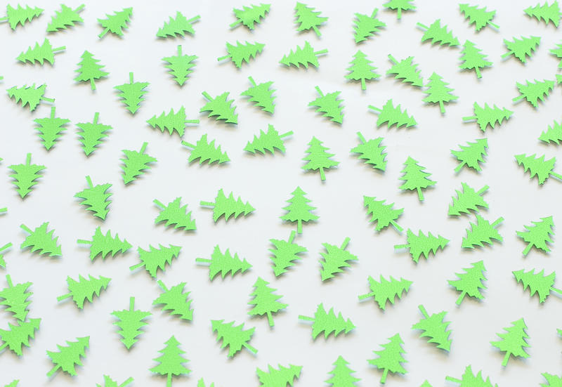 a background of randomly scattered green christmas pine tree shapes