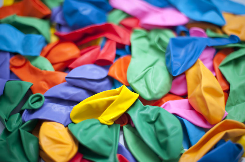 a background of assorted brightly colored party balloons