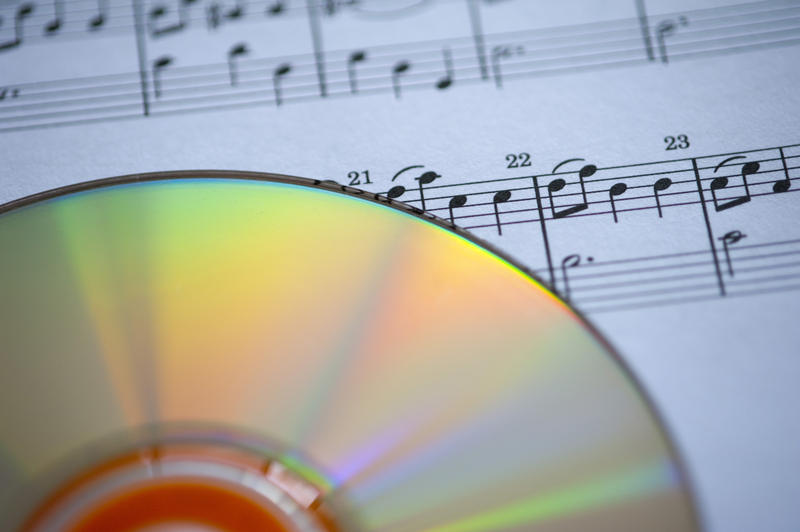 multicoloured reflectings from the surface of a CD, pictured with a narrow depth of field against a background of sheet music