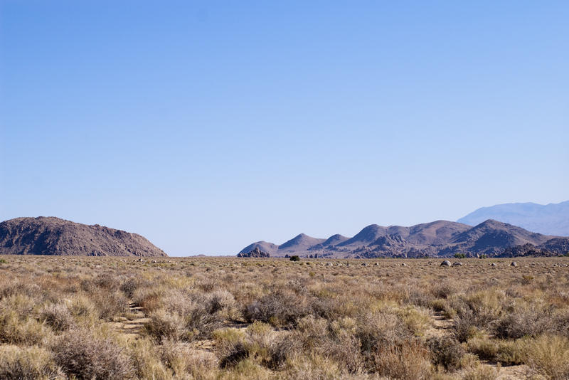 a flat desert landscape with hills and mountains in the distance