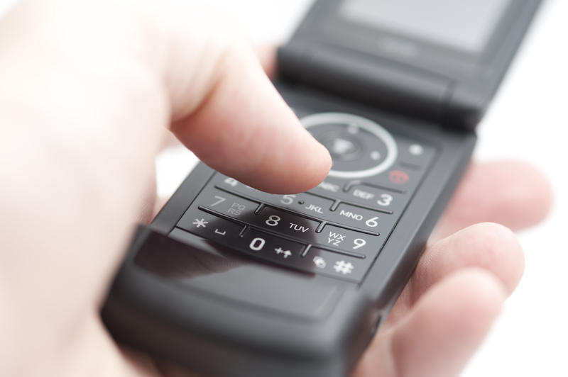 holding a black coloured flip phone with thumb about to press a button on the keypad