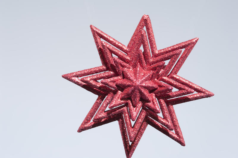 a sparkling christmas star decoration on a grey backdrop