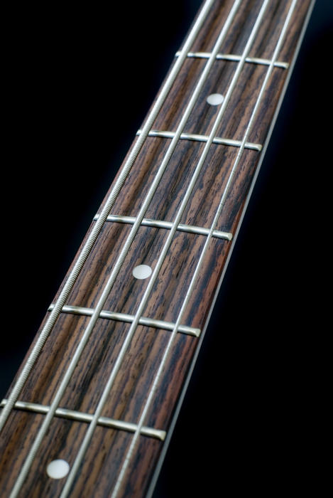 the neck of a bass guitar on a black backdrop