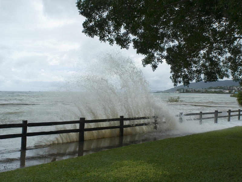 waves breaking over a seawall during a high tide