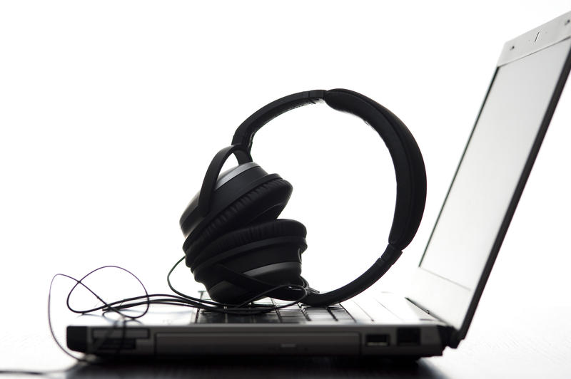 a pair of stereo headphones laid on a laptop keyboard