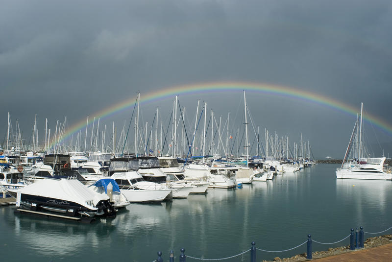 a rainbow and dark storm clouds over yachts in a marina