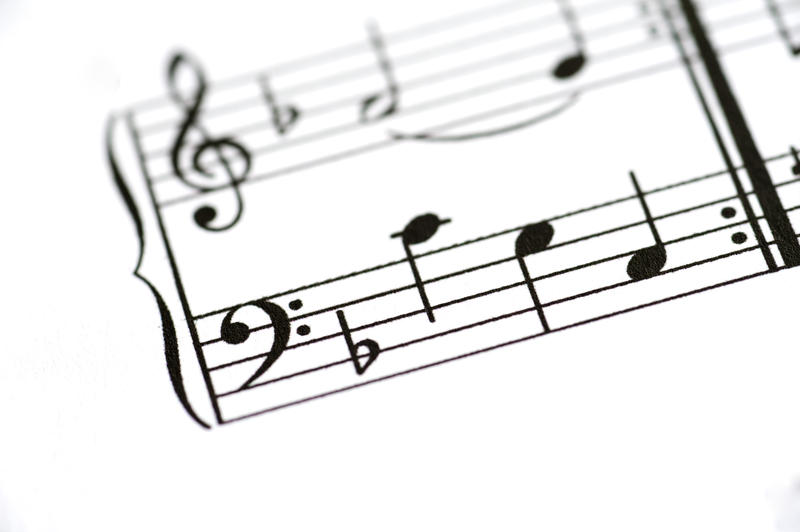 a close up image of a sheet of printed music with the focus on the base clef on a music staf