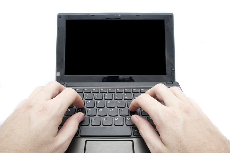 two hands typing on a small netbook computer