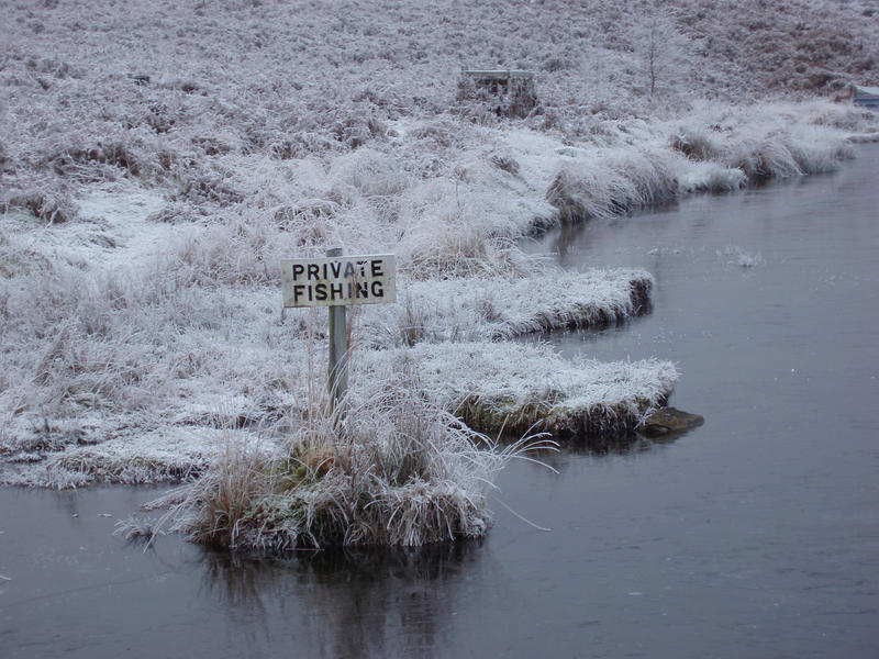 a private fishing sign by a frozen lake