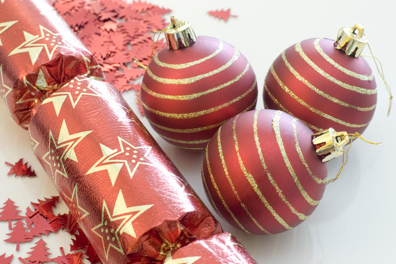 red christmas balls or baubles, cracker and glitter on a white background