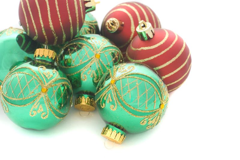 a pile of green and red christmas ball ornaments on a white background