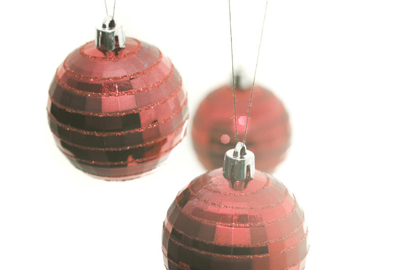 a high key image of three red hanging christmas balls