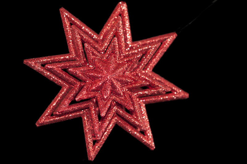 a red coloured christmas star shaped decoration on a black backdrop