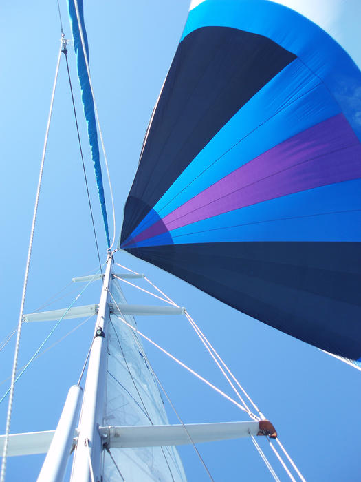 looking up at a yacht mast with its colorful spinnaker catching the wind