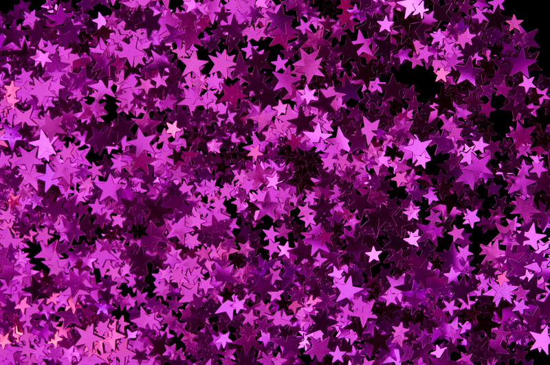 a colorful reflective backdrop of magenta pink metallic confetti stars