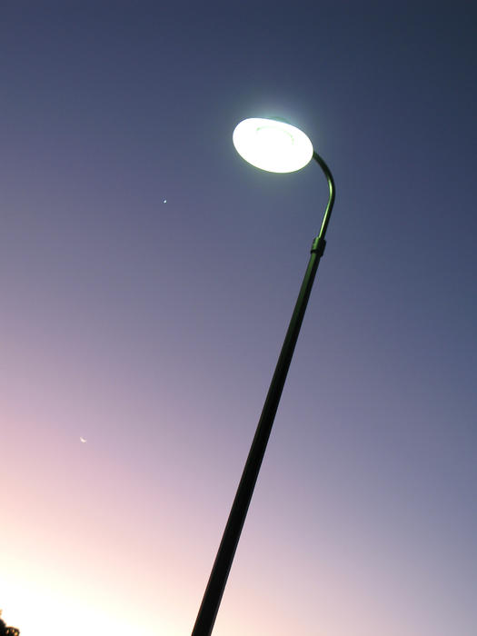 an illuminated streetlamp against a twilight sky