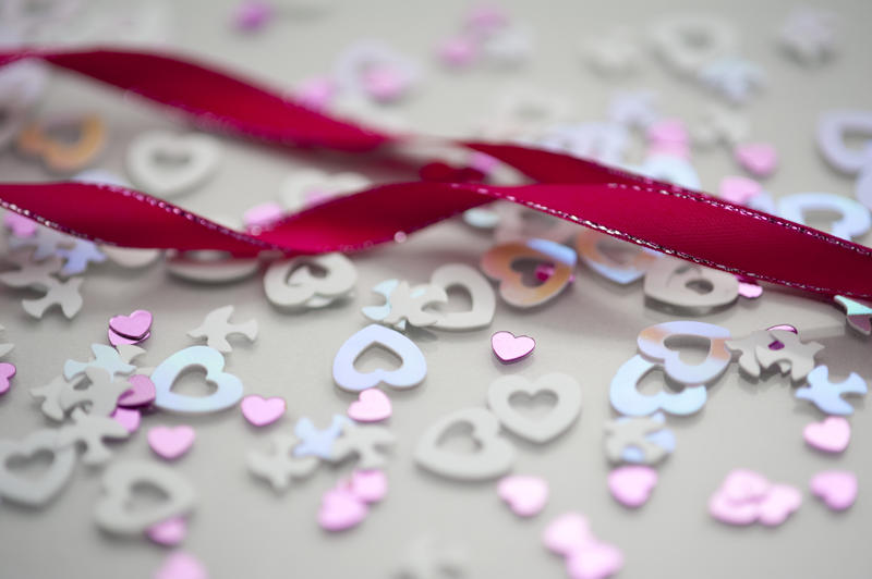 a background image of pink twisted ribbon and wedding confetti shapes
