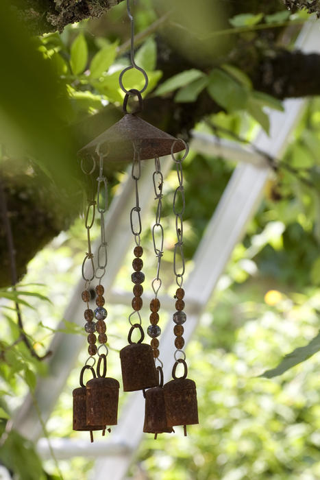 decoraive wind chimes hanging in a garden